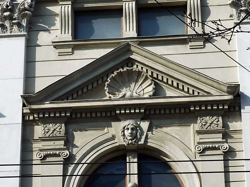 Арка з маскароном дівчини і фронтон вікна